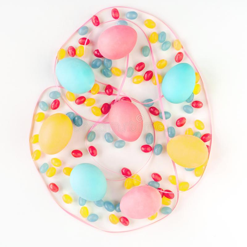 Easter egg concept. Colorful eggs and candies with pink satin ribbon on isolated white background. Flat lay. royalty free stock photography