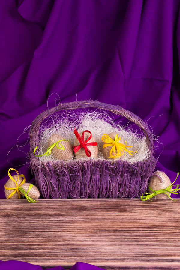 Easter egg decorative in twine in purple basket on wooden table on purple background. Copy space. Easter egg decorative in twine in purple basket on wooden royalty free stock images