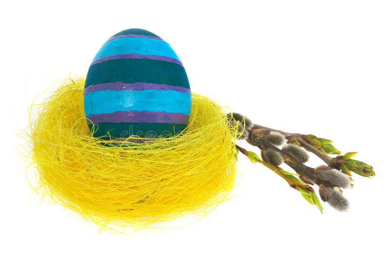 Easter egg hand painted in yellow bird`s nest with blooming twig stock photos