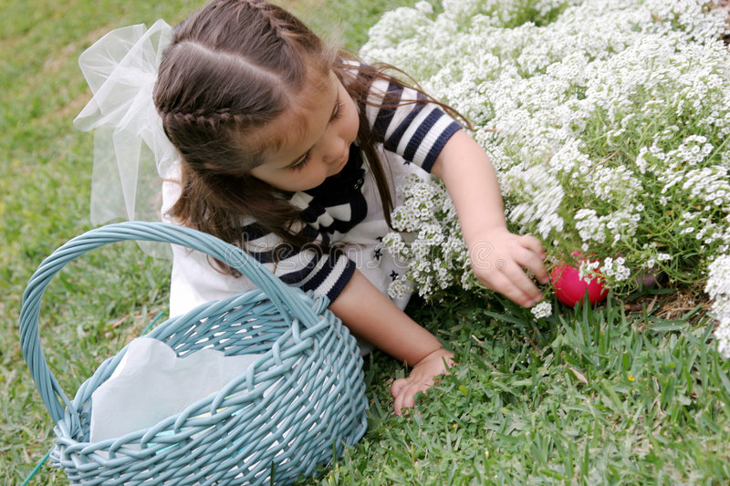 Easter Egg Hunting. Young child hunting for easter eggs stock photography