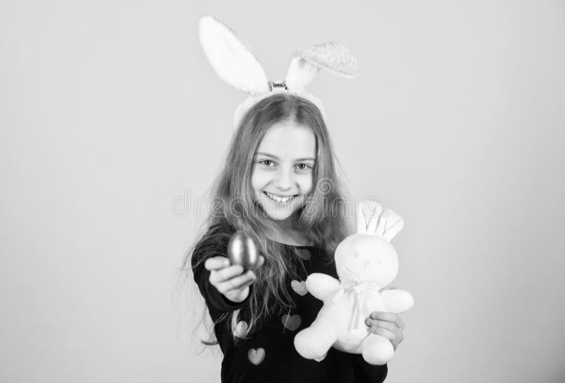 Easter egg hunts as part of festival. Origin of easter bunny. Easter symbols and traditions. Playful child with soft toy. Meet spring holiday. Girl little stock photography