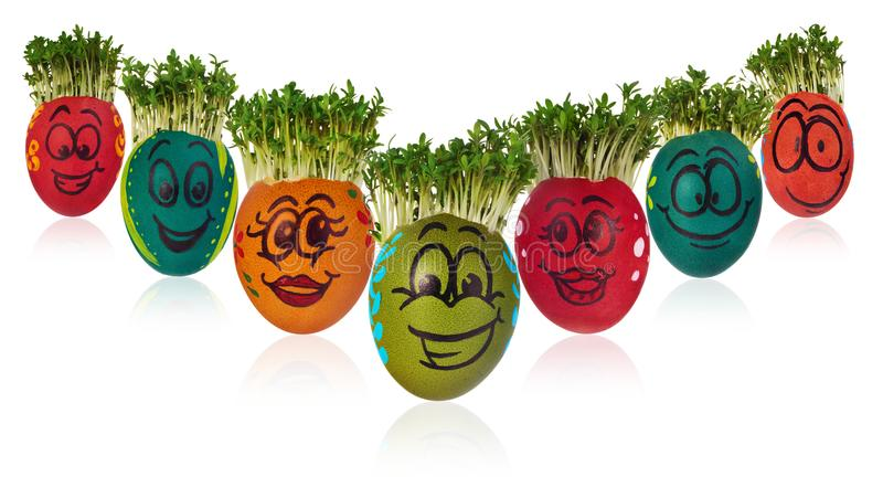 Easter egg painted in a funny smiley girl face and colorful patterns with cress like hair. stock photo