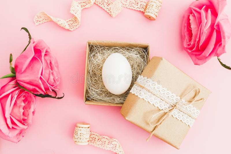 Easter egg in paper gift box and roses flowers on pastel pink background, top view, flat lay, Easter holiday concept. royalty free stock photography