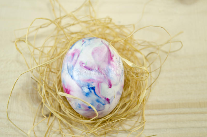 Easter egg on a thatch. Hand painted Easter egg on wooden table stock photos