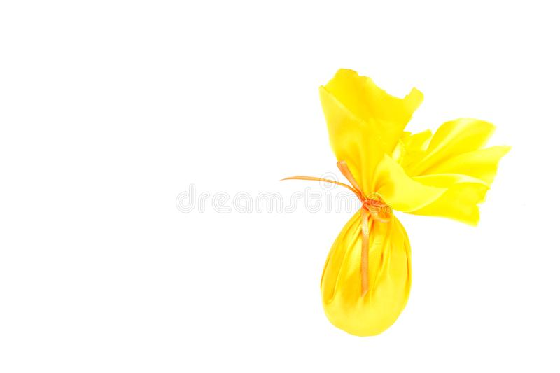 Easter egg, tied in a yellow wrapping fabric with a ribbon, on a white background, the concept of a gift for the holiday Easter stock photo