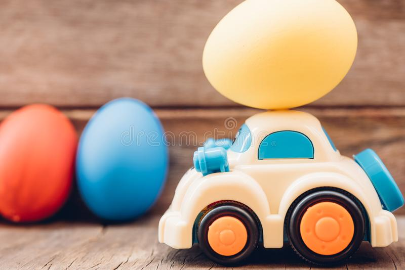 Easter egg and toy car on wooden background stock photo