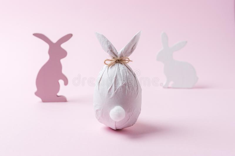Easter egg wrapped in a paper in the shape of a bunny with bunnies decoration. Minimal Easter concept stock images