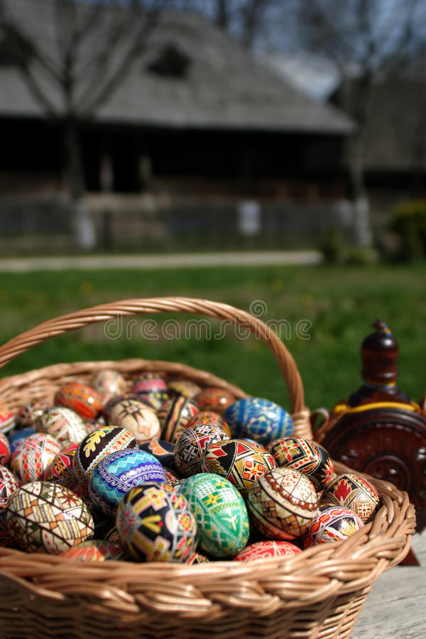 Easter eggs. In a basket and a old house in background royalty free stock images