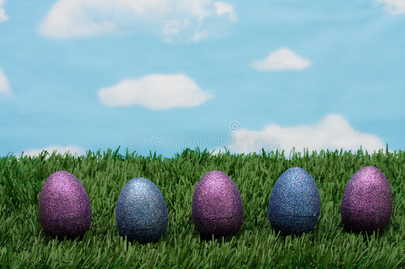 Easter Eggs. Blue and purple sparkle Easter eggs sitting on green grass background, Easter Eggs stock photography