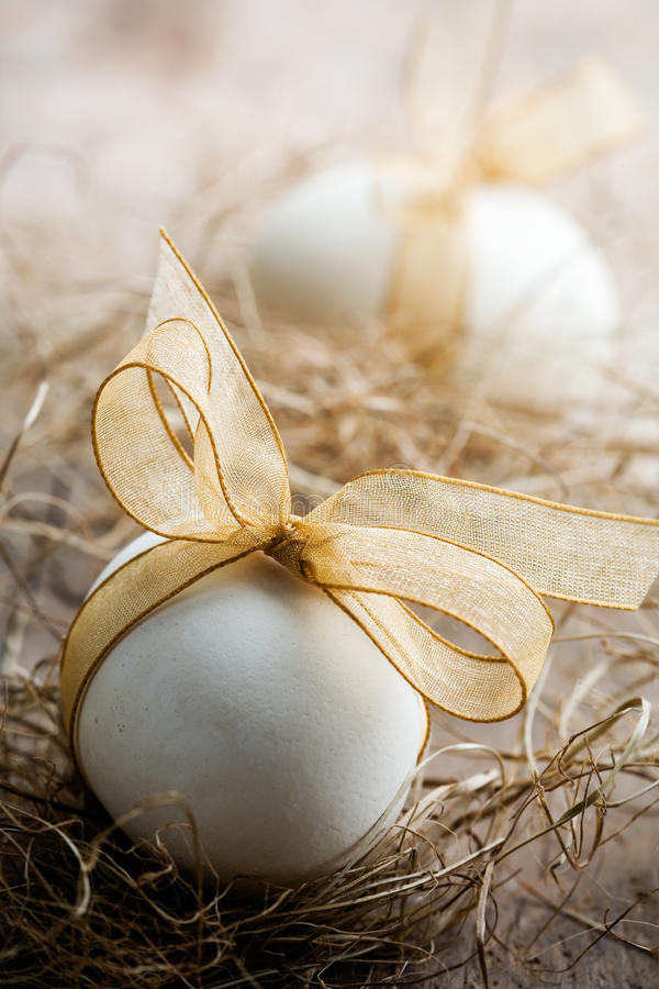 Easter eggs. White easter eggs with beautiful golden bow stock images