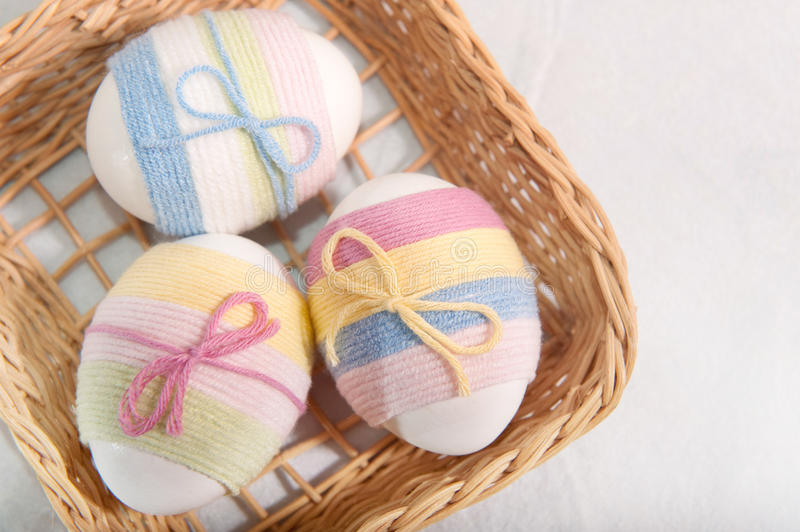 Easter eggs. Three yarn wrapped Easter eggs in basket stock photography