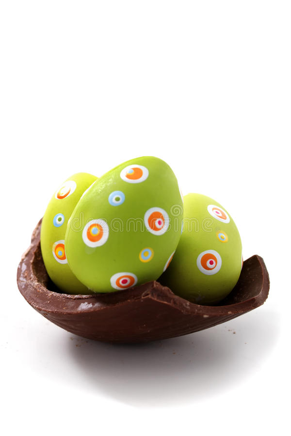 Easter eggs. On a broken piece of chocolate egg on white background stock photography