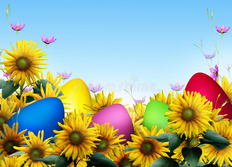 Easter eggs. Brightly colored easter eggs among sunflowers with a bright blue background