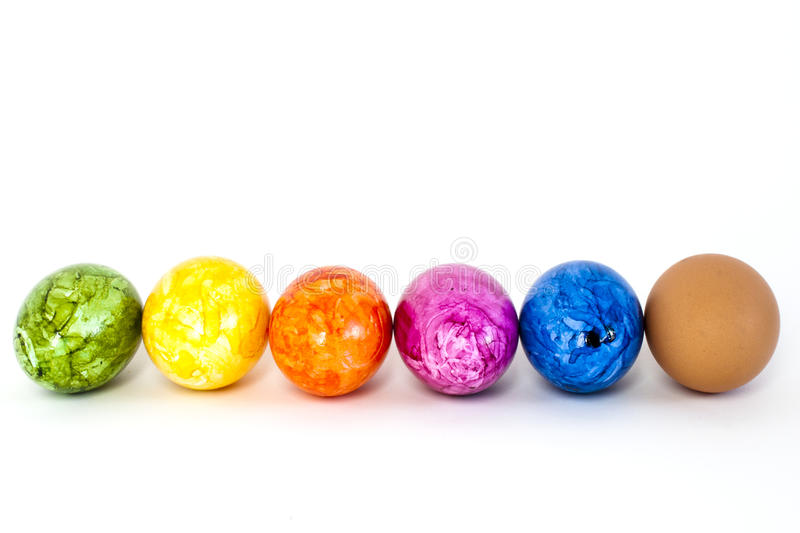 Easter eggs. Coloured eggs and one normal egg in a row royalty free stock photography