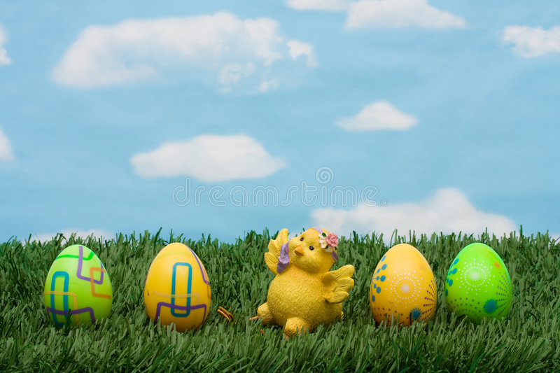 Easter Eggs. Colourful Easter eggs sitting with a chicken on green grass background, Easter Eggs royalty free stock photography