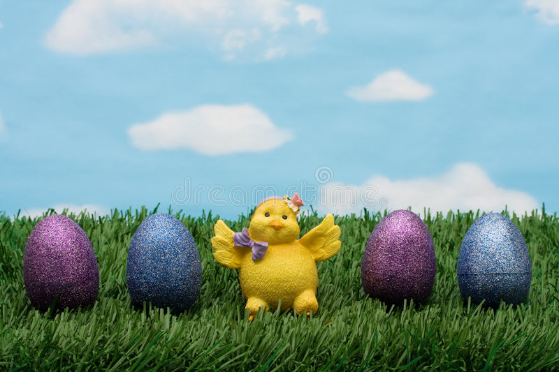 Easter Eggs. Blue and purple sparkle Easter eggs sitting with a chicken on green grass background, Easter Eggs stock photos