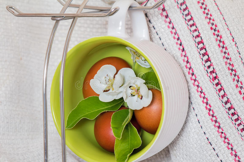 Easter eggs and Apple blossoms. The dyed red Easter eggs and Apple blossoms are installed in large ceramic cups stock image