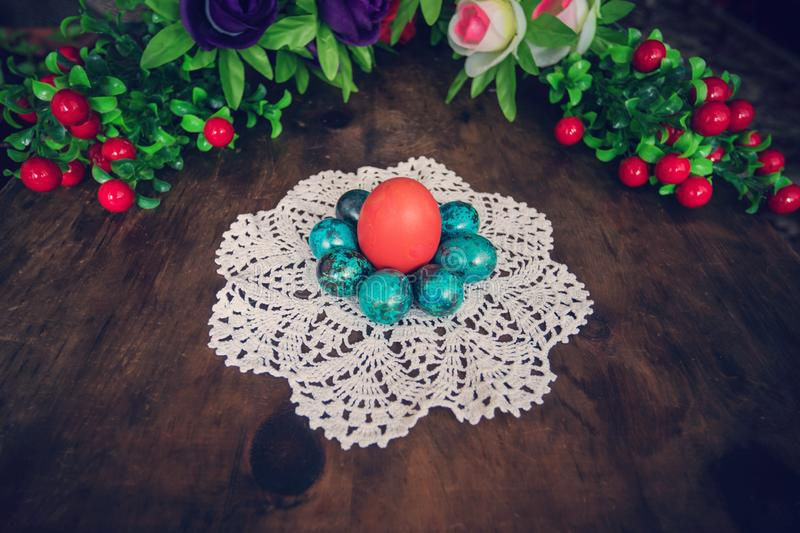 easter eggs on the background of wooden boards. Red chicken egg surrounded by small blue quail eggs on a white tablecloth. stock photography
