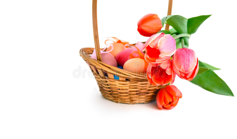 Easter eggs in basket and bunch of pink tulips stock photo