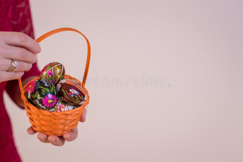 Easter eggs in basket and colorful tulips in hand royalty free stock images