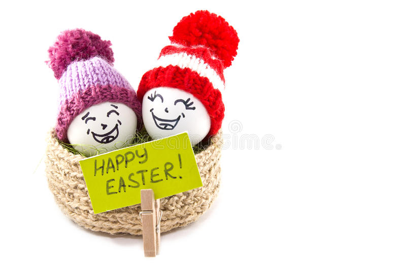 Easter eggs in a basket. Emoticons in knitted hats with pom-poms. Knitted basket of jute, sisal green. Handmade. White background. Isolated royalty free stock photo