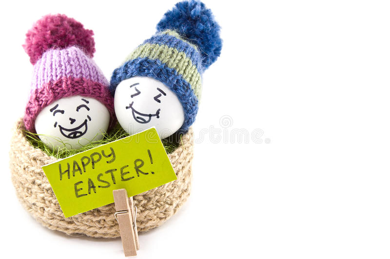 Easter eggs in a basket. Emoticons in knitted hats with pom-poms. Knitted basket of jute, sisal green. Handmade. White background. Isolated stock images