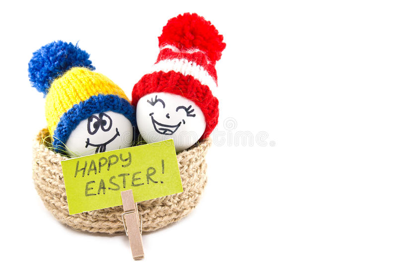 Easter eggs in a basket. Emoticons in knitted hats with pom-poms. Knitted basket of jute, sisal green. Handmade. White background. Isolated stock image