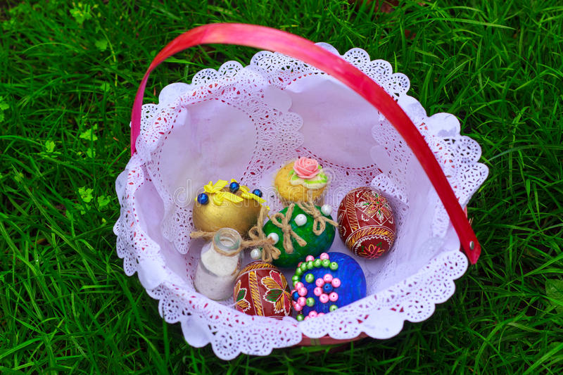 Easter eggs in a basket. In the green grass stock photo