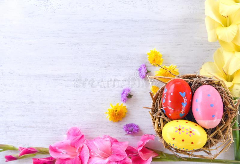 Easter eggs in basket nest decoration with colorful Gladiolus flowers on white background stock image