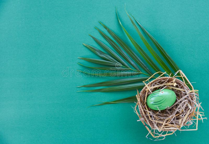 Easter eggs in basket nest decoration with green palm leaves on green background royalty free stock photos