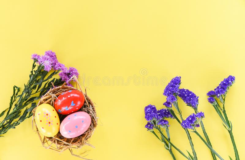 Easter eggs in basket nest decoration with purple flower Marguerite and statice flowers on yellow background stock photos