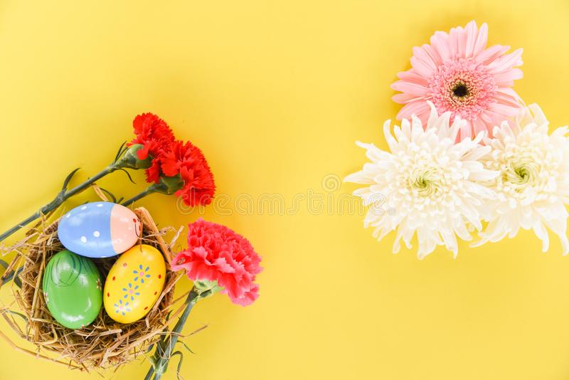 Easter eggs in basket nest decoration with red carnation flower spring summer and pink white gerbera stock images