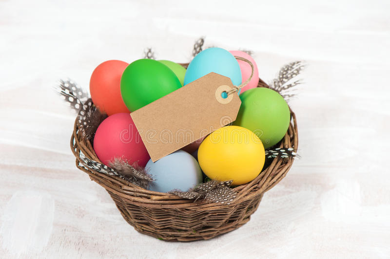Easter eggs in basket over wooden background stock photography