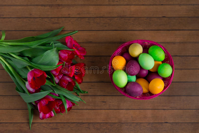 Easter eggs in basket and tulips on wooden table royalty free stock image