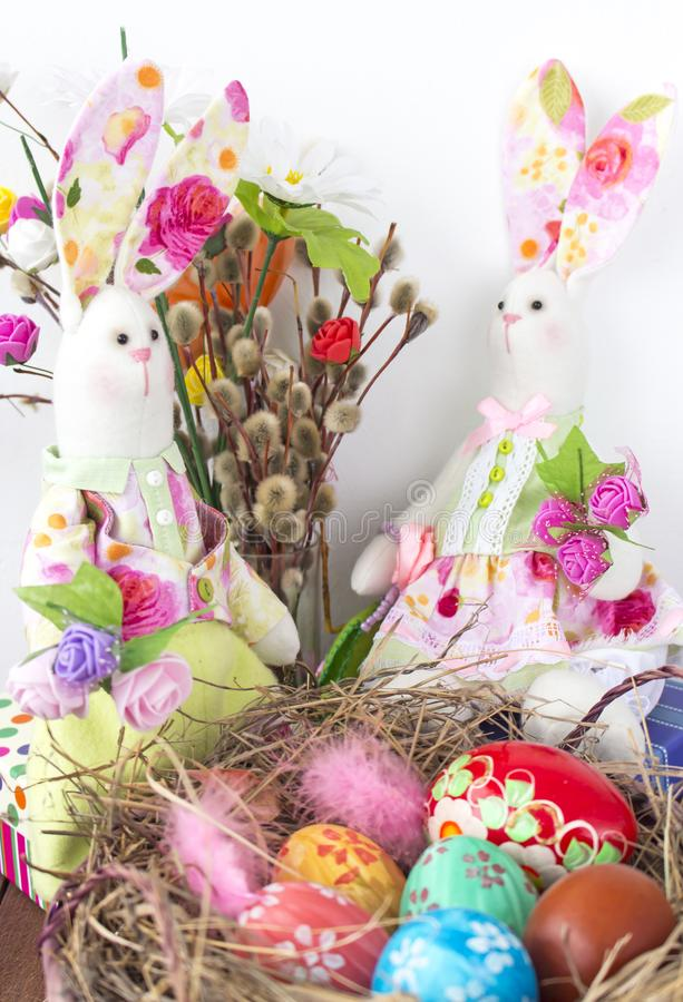 Rabbits look at the basket with colorful eggs for Easter stock photo