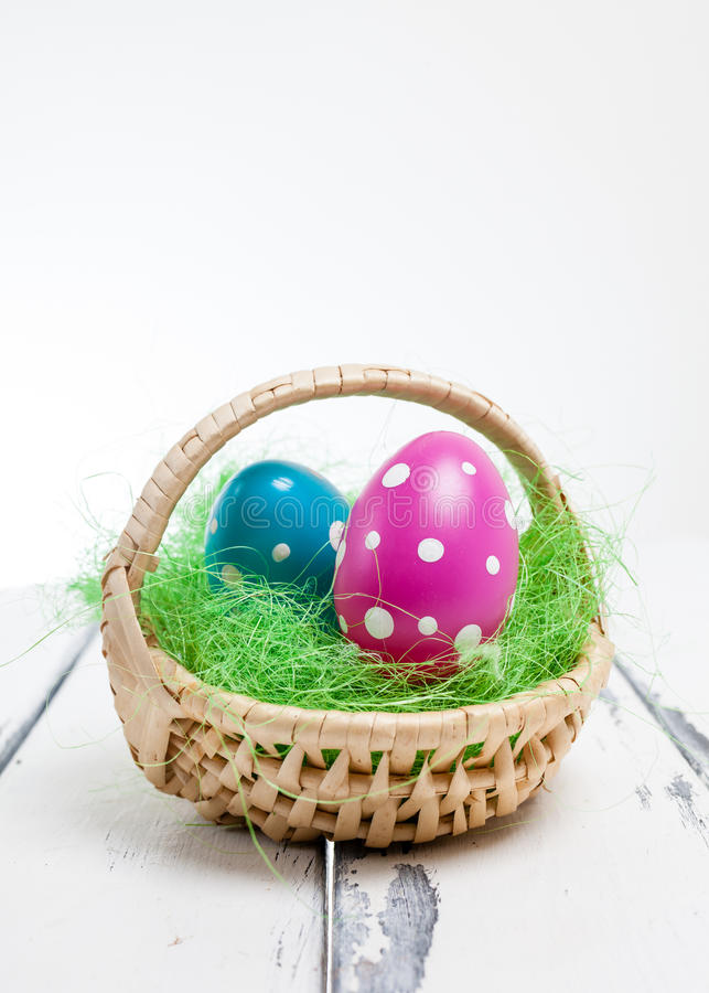 Easter eggs in a basket on white wooden vintage background royalty free stock images