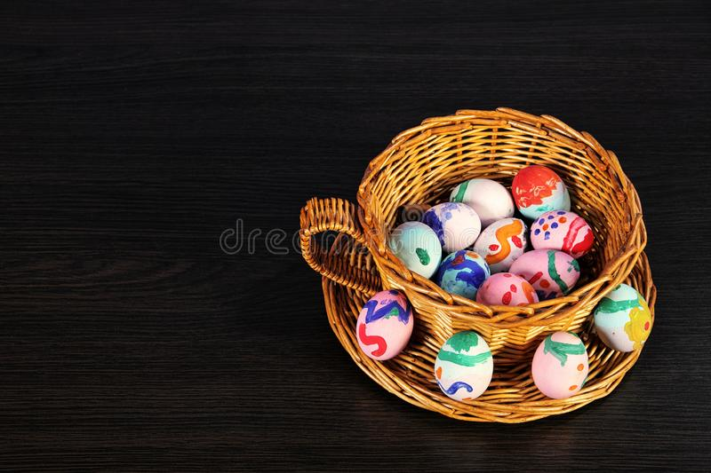 Easter eggs in the basket. wicker basket of straw. festive meal on a dark wooden table stock photo