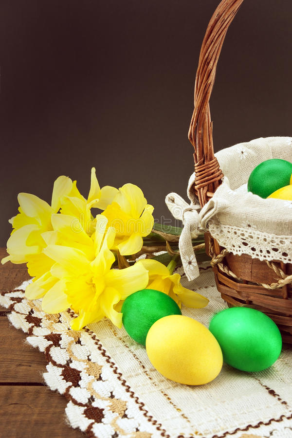 Easter eggs in the basket on wooden table with bouquet of daffodil royalty free stock image