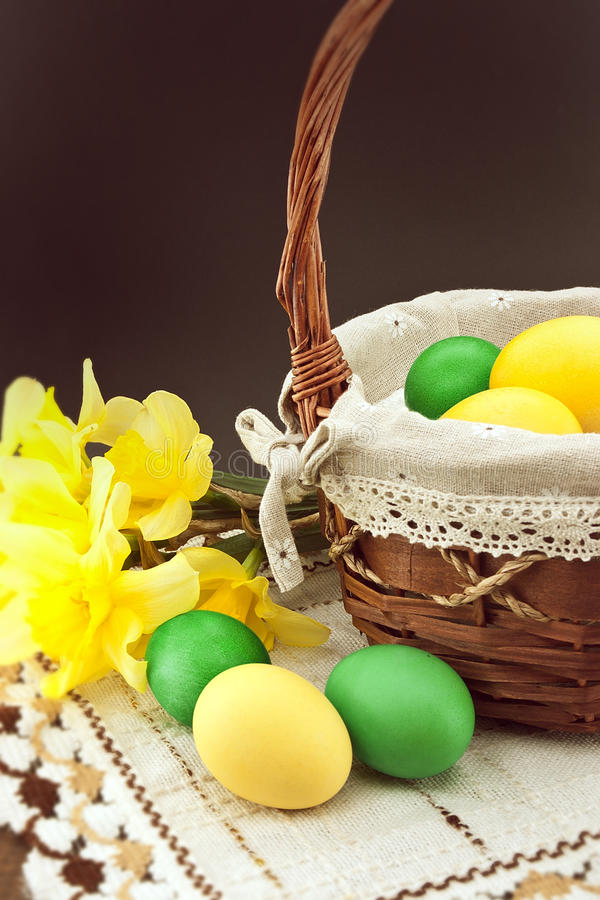 Easter eggs in the basket on wooden table with bouquet of daffodil royalty free stock photos