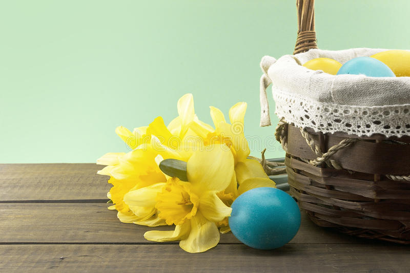 Easter eggs in the basket on wooden table with daffodil royalty free stock photo