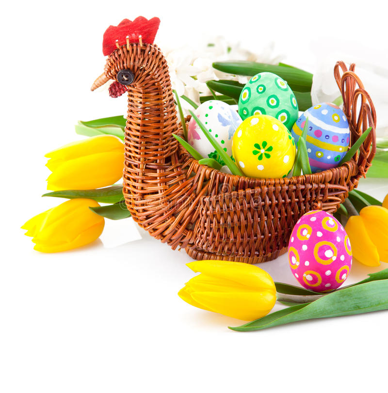 Easter eggs in basket with yellow tulip flowers stock images