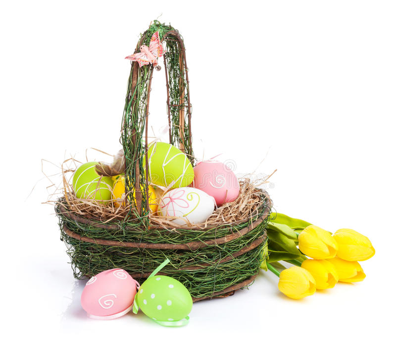 Easter eggs basket and yellow tulips royalty free stock photography