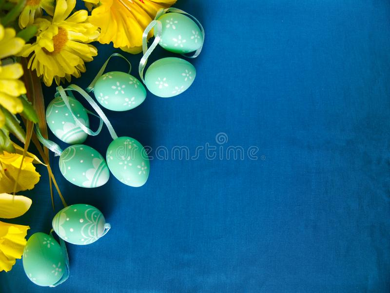 Easter eggs on blue silk, with yellow flowers. royalty free stock image