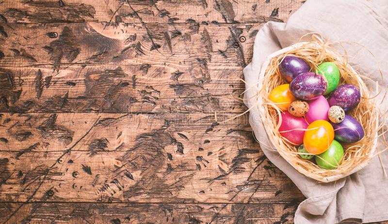 Easter eggs in a bowl. On rustic wooden background, top view stock photography