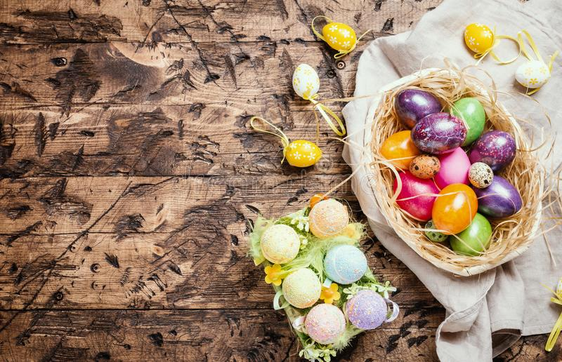 Easter eggs in a bowl. On rustic wooden background, top view stock images