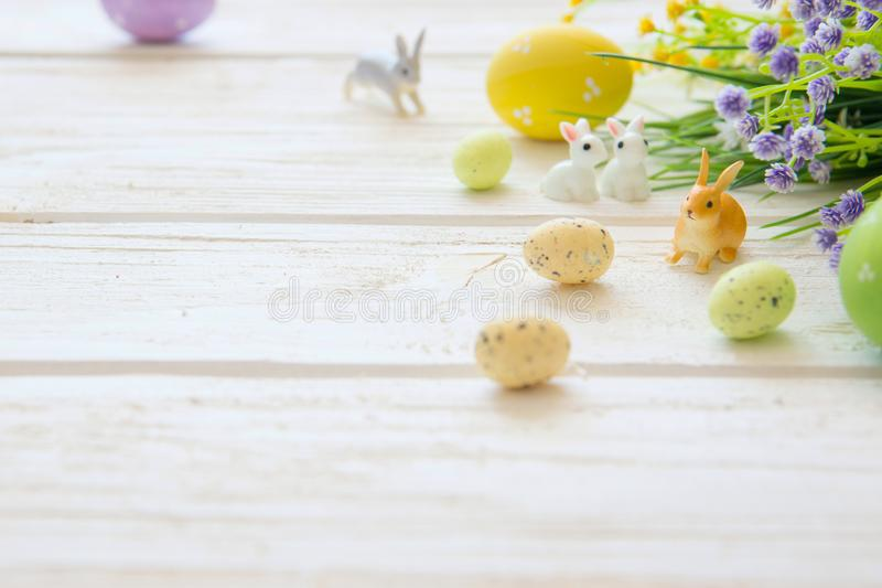 Easter eggs and branch with flowers on wooden. Rabbits toys royalty free stock images