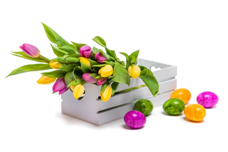 Easter eggs and a bunch of colorful tulips in a white wooden box on a white background stock photos