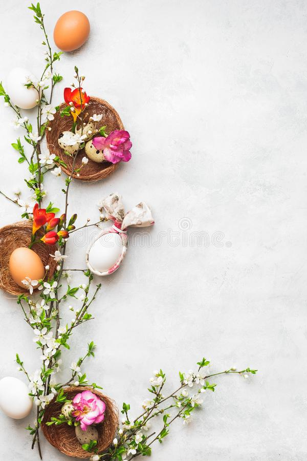 Easter eggs with bunny ear napkin and spring cherry flowers stock photos
