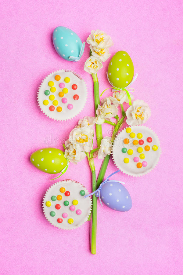 Easter eggs, cake and pretty daffodils flowers on pink background, top view. royalty free stock images