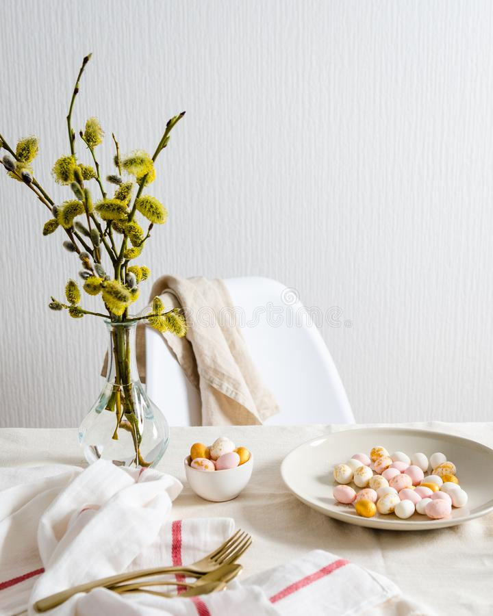Easter eggs candies on the plate on the table with bouquet of willow, copy space for text. Side view, easter card, holiday concept. Easter eggs candies on the stock photo
